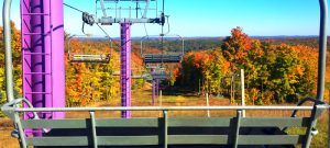 purple chairlift overlooking fall colors