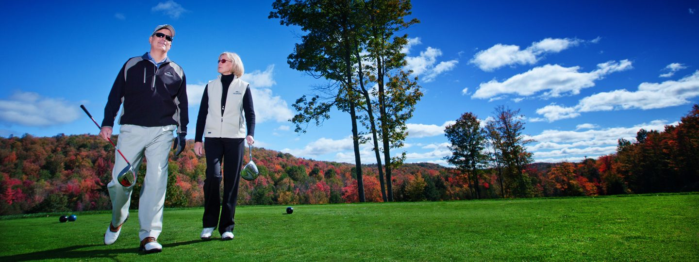 Couple Golfing with Fall Foliage Behind