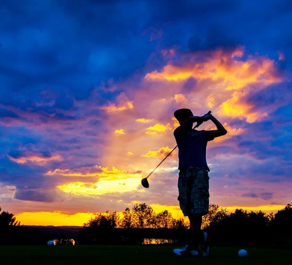 Man teeing off on The Legend hole 3 at Sunset