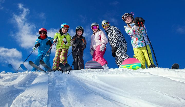 group of children skiing and snowboarding