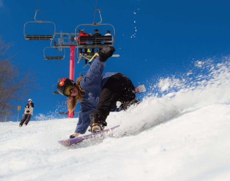 snowboarder carving near pink lift
