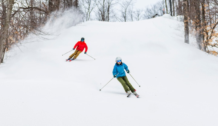 couple skiing down Schuss Mountain