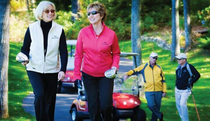 Pair of ladies walking with golf clubs