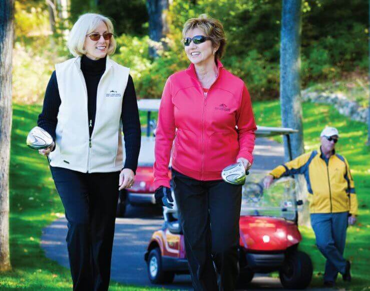 Pair of ladies walking with golf clubs