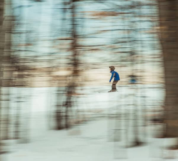 Boy skiing in the trees