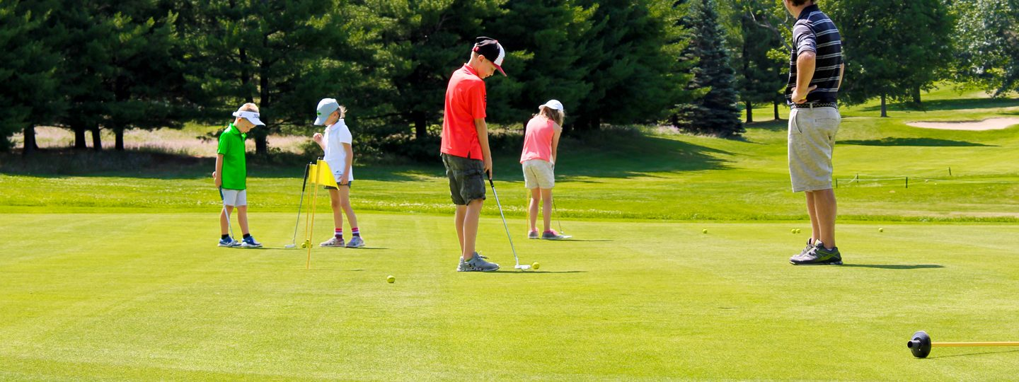 Junior golfers on putting green