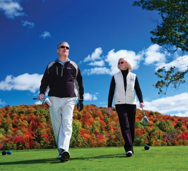 Couple holding golf clubs with fall foliage behind them