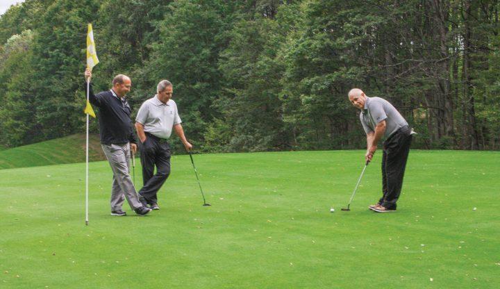 Golf pros putting on green