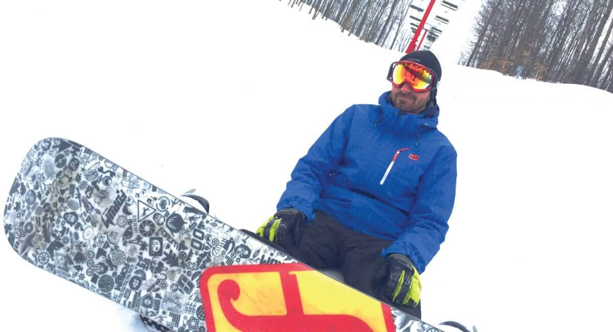 Snowboarder sitting near red chairlift