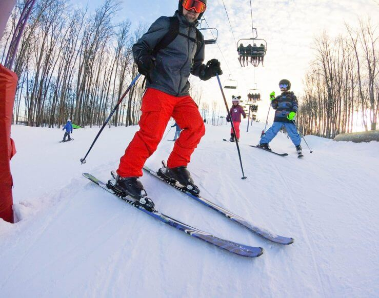 Skier with kids near purple lift tower