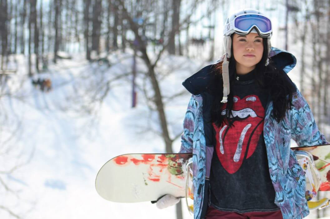 Female snowboarder holding board