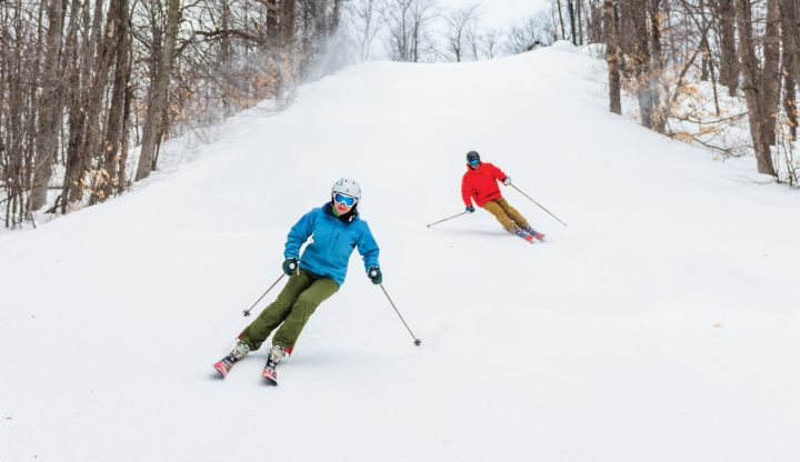 Man and Woman Skiing Down Hill