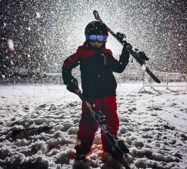 Young Boy Posing with Skis at Night