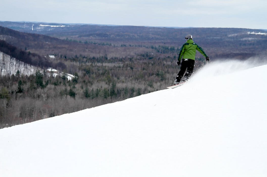 Snowboarder in green jacket on top of Schuss Mountain