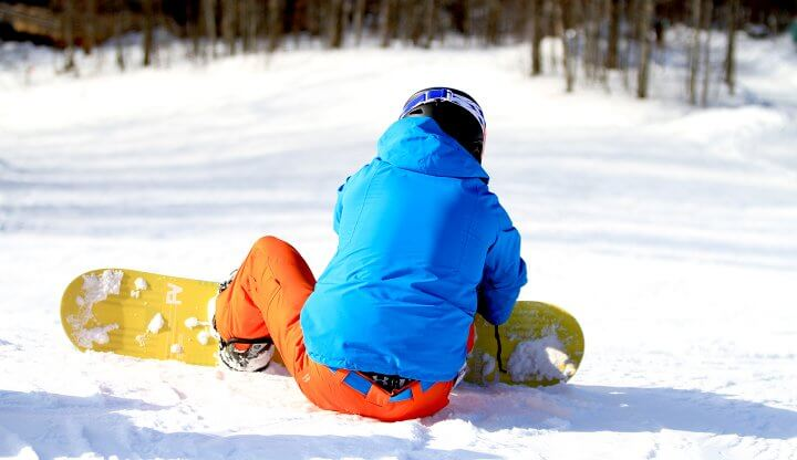 Snowboarder's back looking down the hill