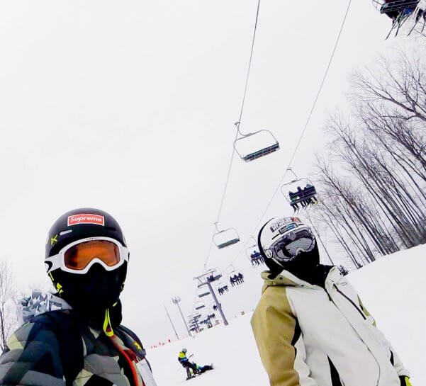 Two snowboarders under the purple lift