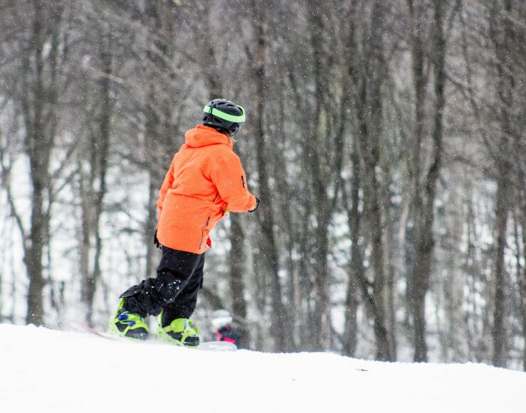 Snowboarder in orange coat going down the hill