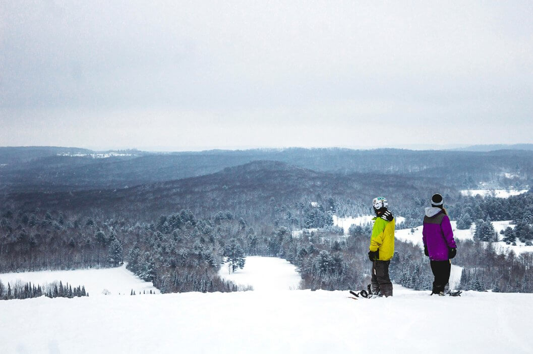 Two snowboarders looking at Schuss Mountain's vista