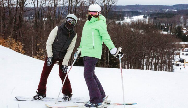 Two skiers pose at the top of Chicken's Choice