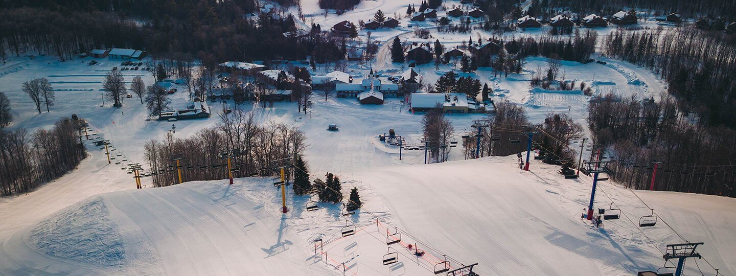 An aerial shot of the top of the yellow and blue chairlift at Schuss Mountain