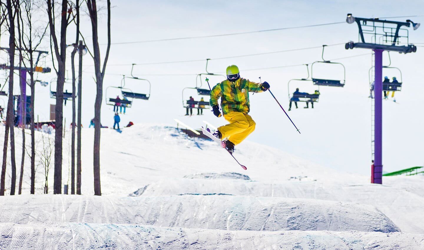 Colorful skier hitting a jump in the Monster Terrain Park