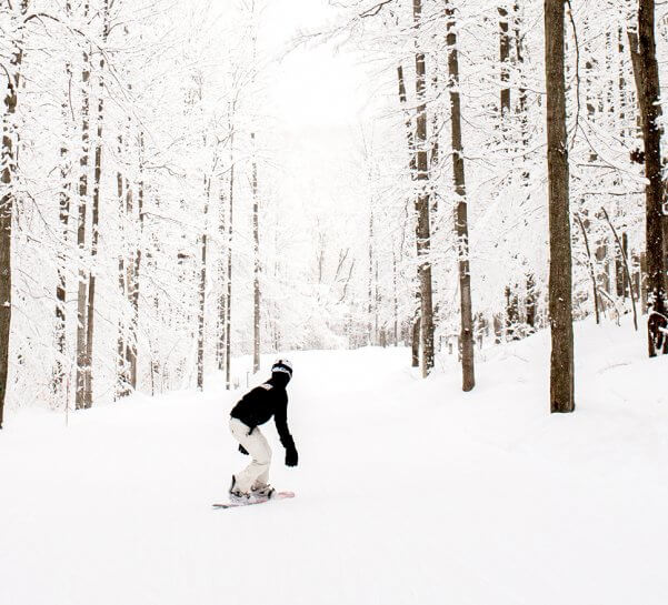 A snowboarder going down River Run
