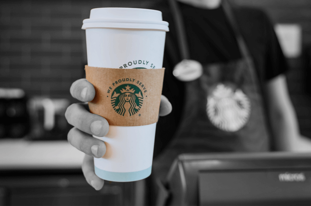 Barista's hand holding a starbucks cup
