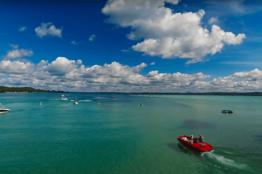 Torch Lake with red boat in foreground
